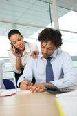 Geschäftsfrau am telefon neben ihr partner — Stockfoto