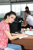 Woman glancing up from her desk in a busy office — Stock Photo
