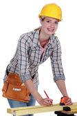 Tradeswoman som visar en mätning på en planka — Stockfoto