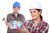 Builders with a house made of money — Stock Photo