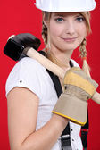 Woman carrying a mallet on her shoulder — Stock Photo
