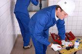 Encanadores trabalhando em uma sala de azulejos — Foto Stock