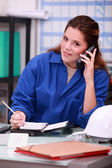 Woman answering the phone in a office — Stock Photo