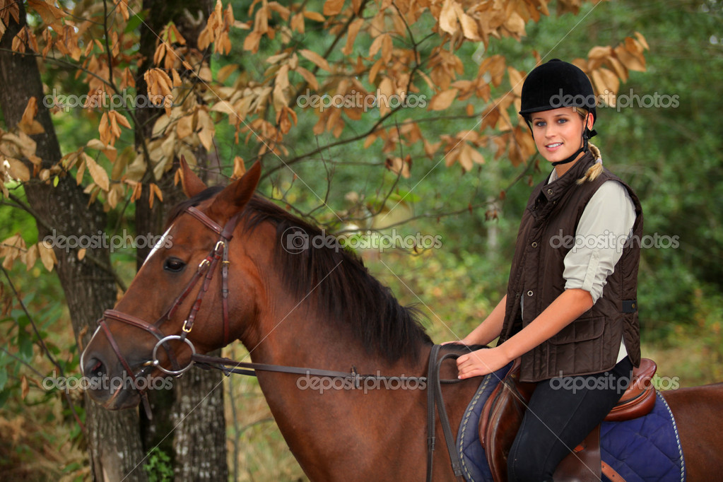 Young woman riding a horse through woodland — Stock Photo #8538186