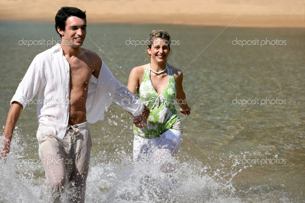 Playful young couple running through water — Stock Photo #8538772