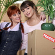 Girls roommates moving into their new apartment — Stock Photo