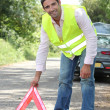 Man in fluorescent vest putting out a warning triangle by a breakdown — Stock Photo #8541710