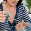 Mature woman taking drugs — Stock Photo