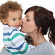 Mother kissing her little boy — Stock Photo