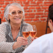 Older woman drinking rose wine in a restaurant with a young man — Stock Photo #8545178