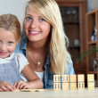 Stock Photo: Mother and daughter playing dominoes