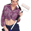 Sexy craftswoman painter holding a roller brush — Stock Photo #8547217