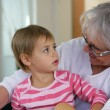 Old lady playing with granddaughter — Stock Photo