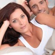 heureux couple pose dans son lit — Photo