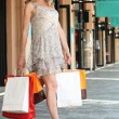 Woman with shopping bags outside boutiques - ストック写真