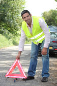Man in fluorescent vest putting out a warning triangle by a breakdown — Stock Photo