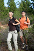 Young couple hiking through the woods — Stock Photo