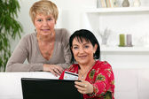 Two middle-aged women shopping online — Stock Photo
