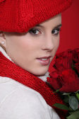 Woman in a red beret with red roses — Stock Photo