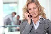 Businesswoman using a cellphone in an office — Stock Photo