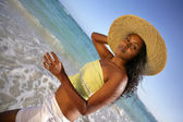 Woman in a large straw hat on the beach — Stock Photo