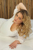 Woman with long blonde hair reclining on a bed — Stock Photo