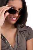 Woman peering over her sunglasses — Stock Photo