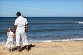 Father and daughter watching the horizon at the beach — Stock Photo