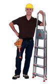 Happy manual worker stood with step ladder — Stock Photo