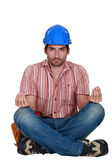 A construction worker in the lotus position. — Stock Photo