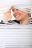 Nosy woman peering through some blinds — Stock Photo