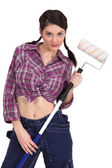 Sexy craftswoman painter holding a roller brush — Stock Photo