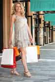Woman with shopping bags outside boutiques — Stock Photo