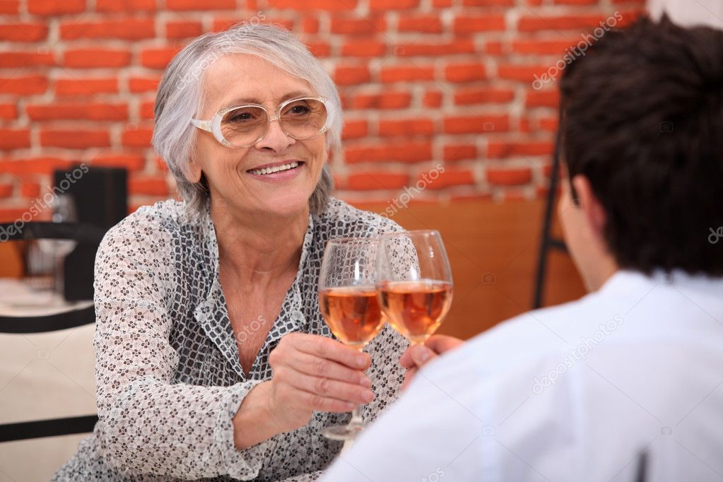 Older woman drinking rose wine in a restaurant with a young man  Stock Photo #8545178
