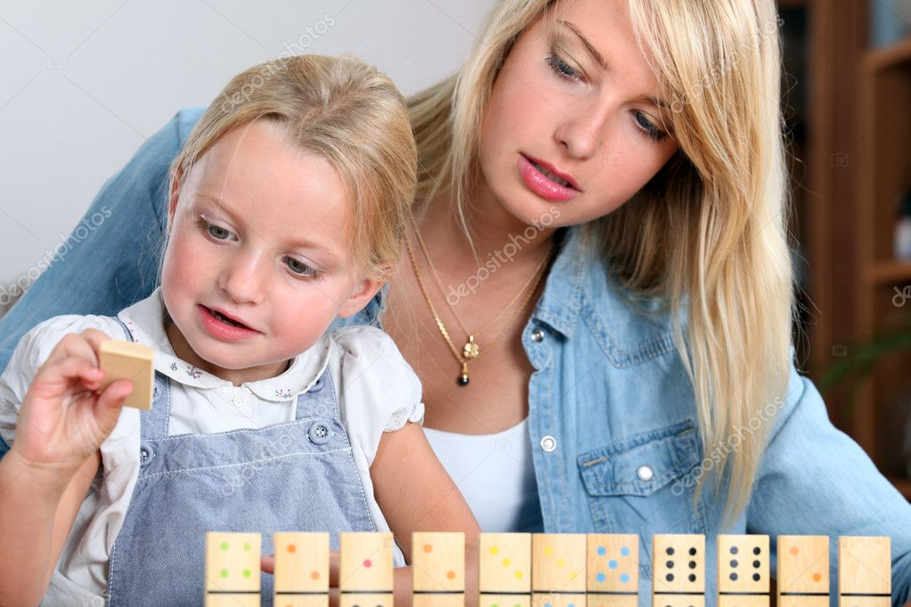 Young girl playing with dominoes — Stock Photo #8545287