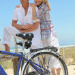 Couple with bikes on the beach — Stock Photo