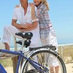 Couple with bikes on the beach — Stock Photo