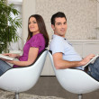 Couple in living room using laptops — Stok fotoğraf
