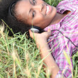 Woman laid in field listening to music — Stock Photo