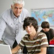 Stock Photo: Teacher helping teen in class