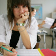 Bored teenager working on her homework — Stockfoto
