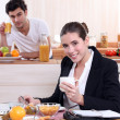 Young couple having breakfast together in kitchen - Stock Photo