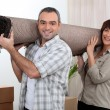 Stock Photo: Couple carrying carpet over shoulders