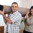 Couple carrying carpet over shoulders — Stock Photo #8553130