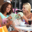 Friends comparing purchases in cafe — Stock Photo #8553144