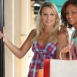 Portrait of 2 girls with shopping bags — Stock Photo