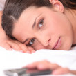 Closeup of a woman in bed reaching for her cellphone — Stock Photo