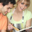 Young man and young smiling while reading cookbook — Stock Photo