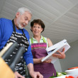 Mature couple cooking with cookbook - Stock Photo
