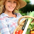 Woman with a straw hat holding basket of vegetables. — Stock Photo #8554586